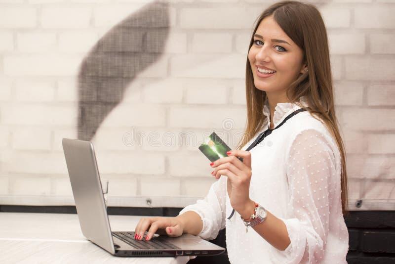 La giovane bella donna sorridente si siede ad una tavola e compra online immagine stock