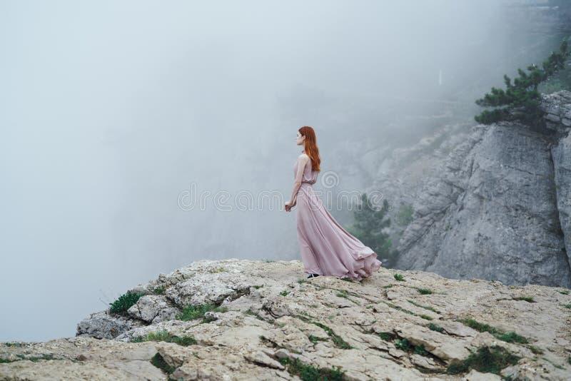 La giovane bella donna in un vestito rosa lungo sta stando vicino ad una scogliera della montagna nella nebbia fotografia stock libera da diritti