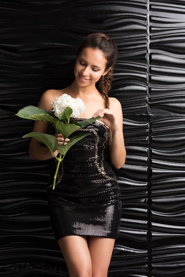 La giovane bella donna vede un fiore bianco Un breve vestito nero immagine stock libera da diritti