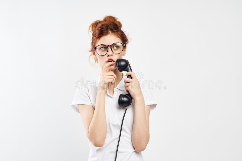 La giovane bella donna in vetri su un fondo isolato bianco tiene un vecchio telefono, comunicazione fotografia stock