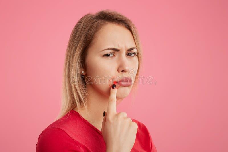 La giovane bella femmina di malcontento con lo sguardo infelice, ha herpes orale, indica alle labbra vicine arrotolate, sta later immagini stock libere da diritti