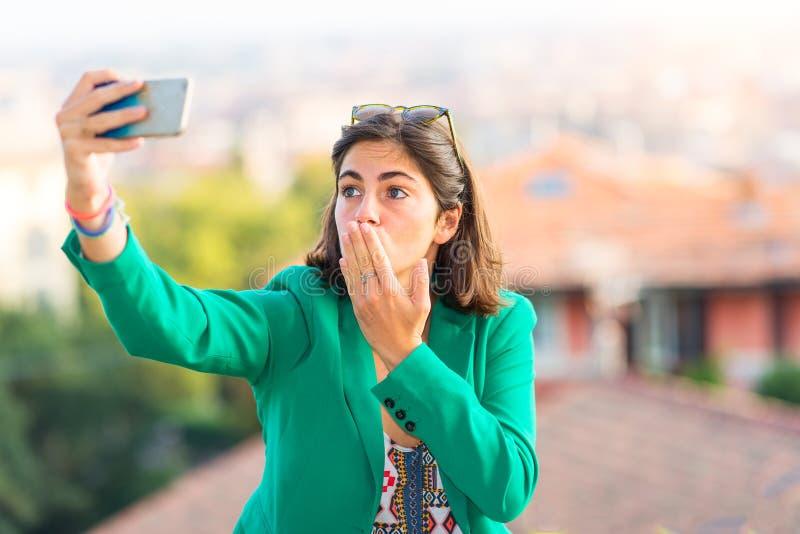 La giovane bella presa della ragazza invia ad un bacio i selfies assenti con mobil fotografia stock