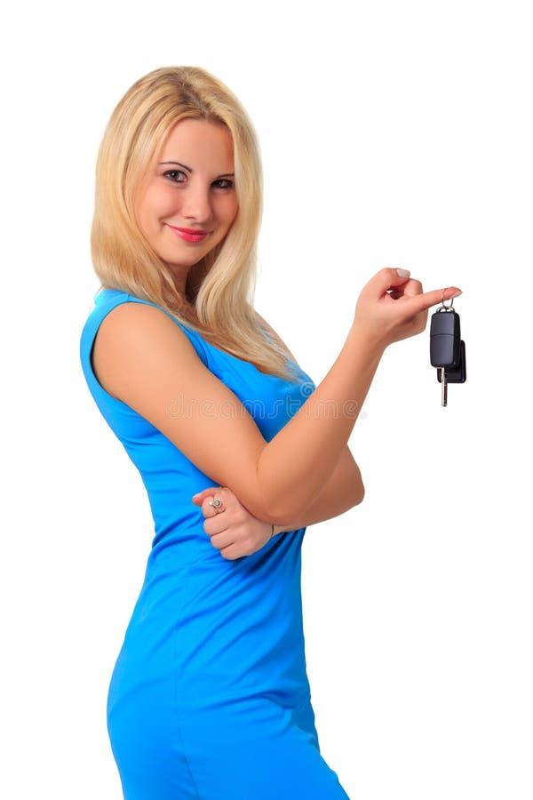 La giovane bella ragazza bionda attraente in vestito blu tiene le chiavi dell'automobile sul dito fotografia stock