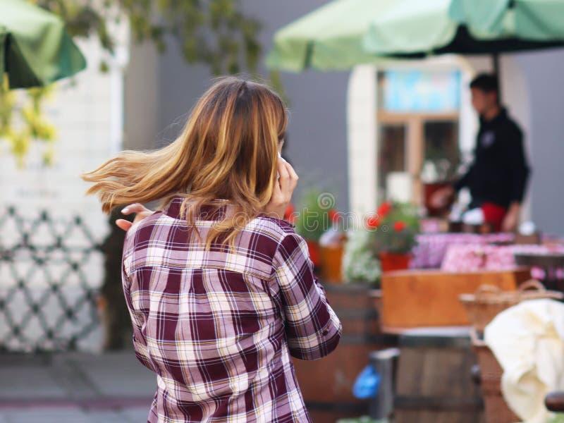 La giovane bella ragazza bionda comunica su uno smartphone nella via di vecchia città Aggeggi nella comunicazione di ogni giorno  fotografia stock