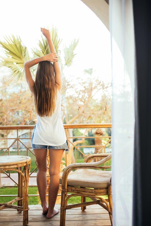 La giovane bella ragazza che si siede su una sedia sul balcone dell'hotel e considera le palme ed il mare immagini stock libere da diritti
