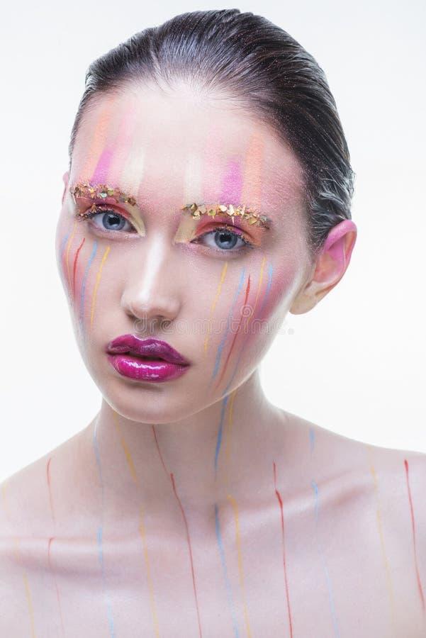 La giovane bella ragazza con multicolore spruzza sul suo fronte immagine stock libera da diritti