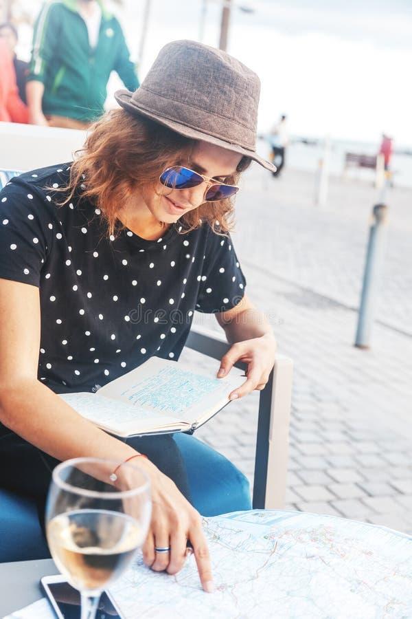La giovane bella ragazza della donna progetta il suo viaggio ad una tavola in un caffè sul lungomare in una città marittima immagine stock