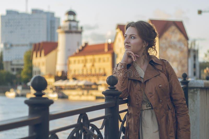 La giovane bella ragazza di affari esamina la città fotografia stock