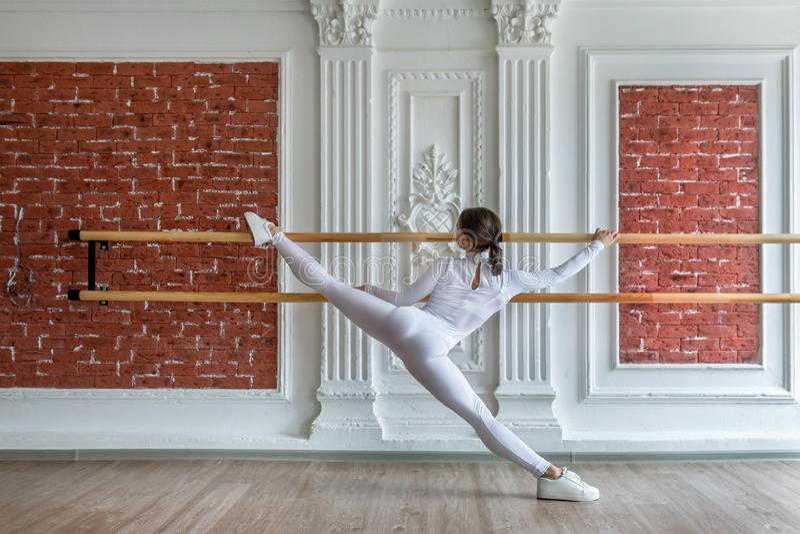 La giovane bella ragazza flessibile in tuta bianca sta posando in uno studio di ballo Tema di balletto del corpo e di allungament fotografie stock libere da diritti
