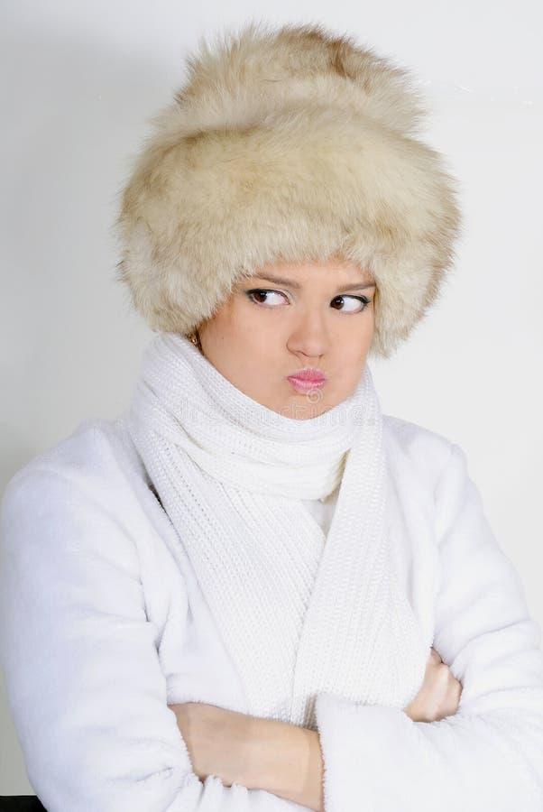 La giovane bella ragazza in pelliccia su un fondo bianco fotografia stock libera da diritti