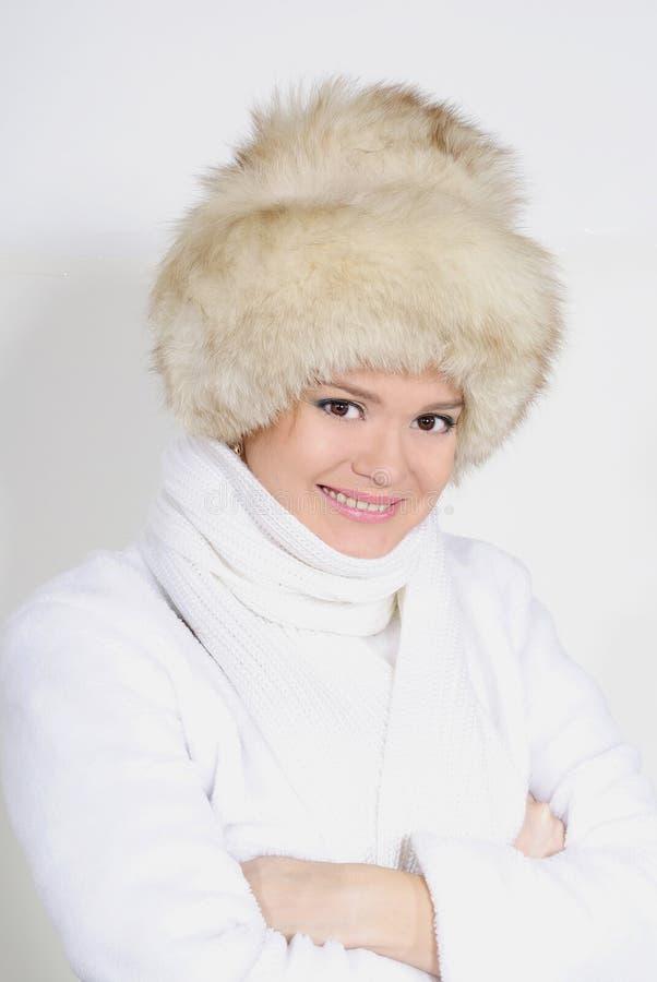 La giovane bella ragazza in pelliccia su un fondo bianco immagine stock libera da diritti