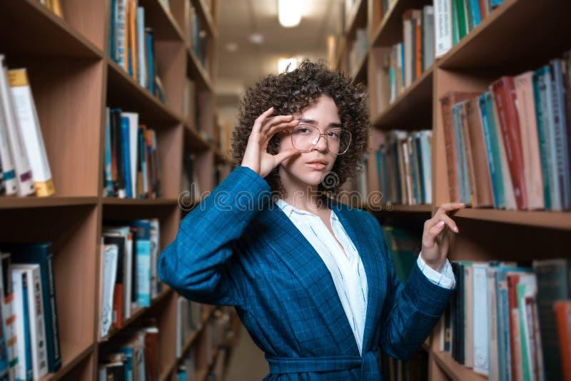 La giovane bella ragazza riccia in vetri ed in un vestito blu sta stando nella biblioteca fotografia stock libera da diritti