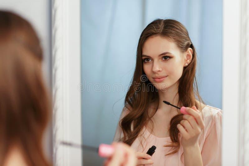La giovane bella ragazza si rende un trucco davanti ad uno specchio immagini stock libere da diritti