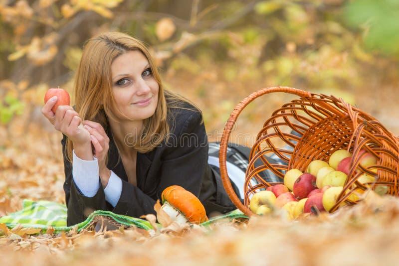 La giovane bella ragazza si trova sopra sul fogliame nella foresta e nella tenuta di autunno della mela in sua mano fotografia stock libera da diritti
