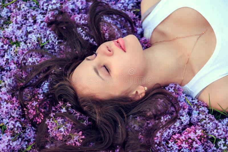 La giovane bella ragazza si trova sui fiori lilla fotografia stock libera da diritti