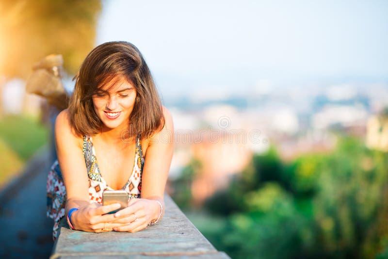 La giovane bella ragazza su una parete in una città invia il messaggio con il soci immagine stock