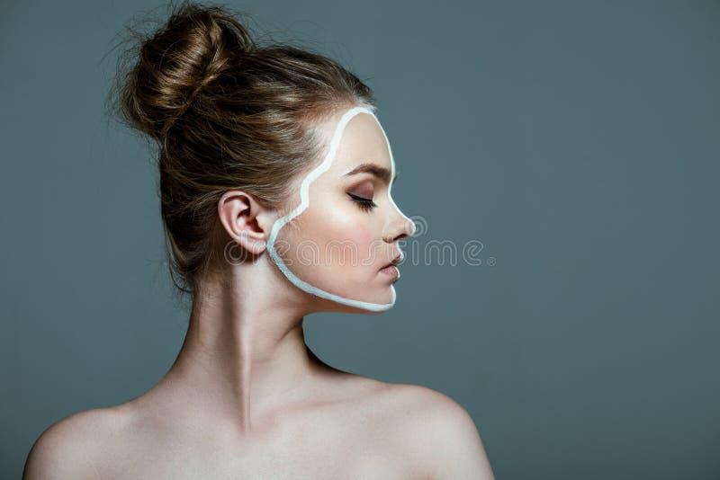 la giovane bella ragazza teenager con gli occhi chiusi ed il body art bianco creativo allineano sul fronte, immagini stock libere da diritti