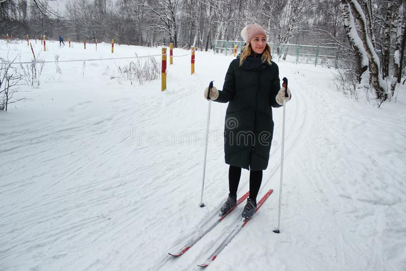 La giovane bella ragazza va sciare nella stagione invernale su un primo piano del pendio dello sci immagini stock