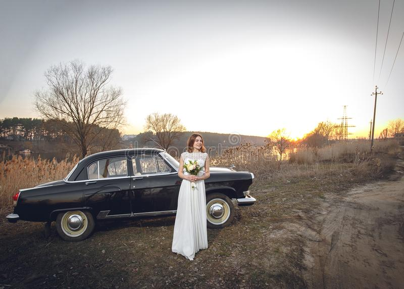 La giovane bella sposa è dopo vicino annerire il retro fondo del tramonto dell'automobile Nozze con la vecchia retro automobile d fotografia stock libera da diritti