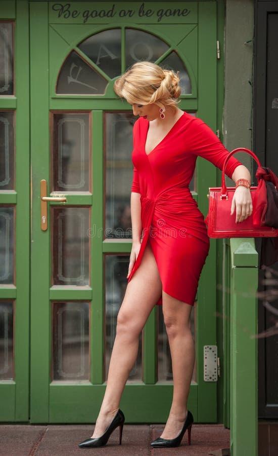 La giovane bionda affascinante in vestito sexy rosso che posa davanti ad un verde ha dipinto la struttura di porta Giovane donna  fotografie stock libere da diritti