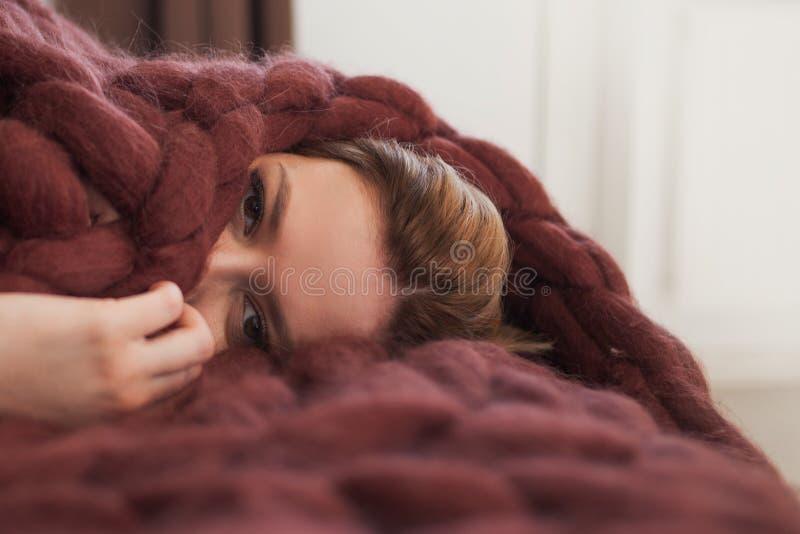La giovane bionda sveglia sta trovandosi sul letto avvolto in una coperta accogliente marrone Calore e comodit? della casa fotografia stock libera da diritti