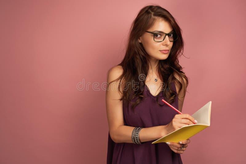 La giovane bruna scrive qualcosa giù in suo taccuino che esamina la macchina fotografica tramite i suoi occhiali, rosa fotografia stock