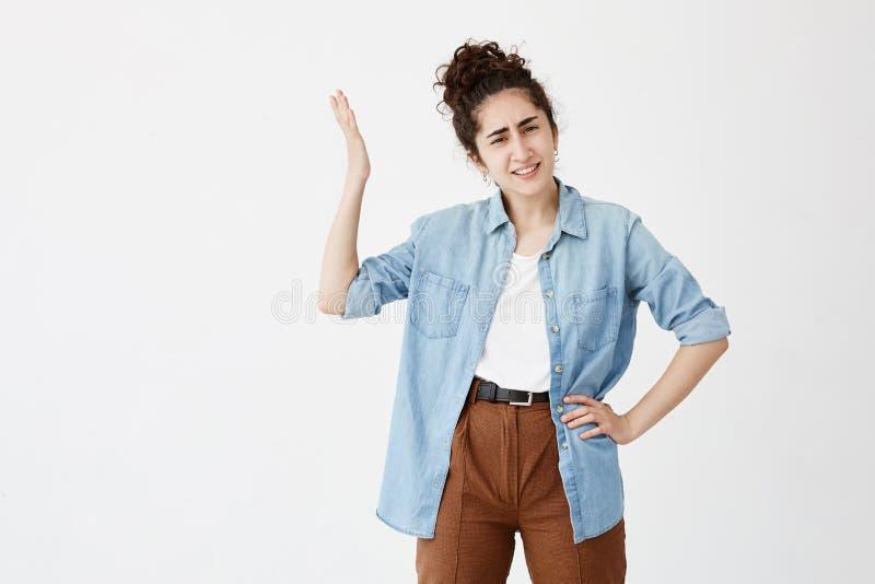 La giovane bruna serra i denti nell'irritazione vestiti in camicia del denim sopra la cima bianca, essendo infastidendo e immagine stock