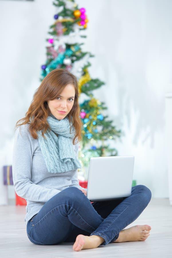La giovane casalinga felice che utilizza il computer portatile nel natale ha decorato il salone immagini stock libere da diritti