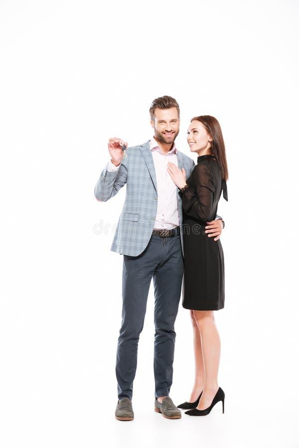 La giovane condizione amorosa sorridente delle coppie ha isolato le chiavi della tenuta immagine stock