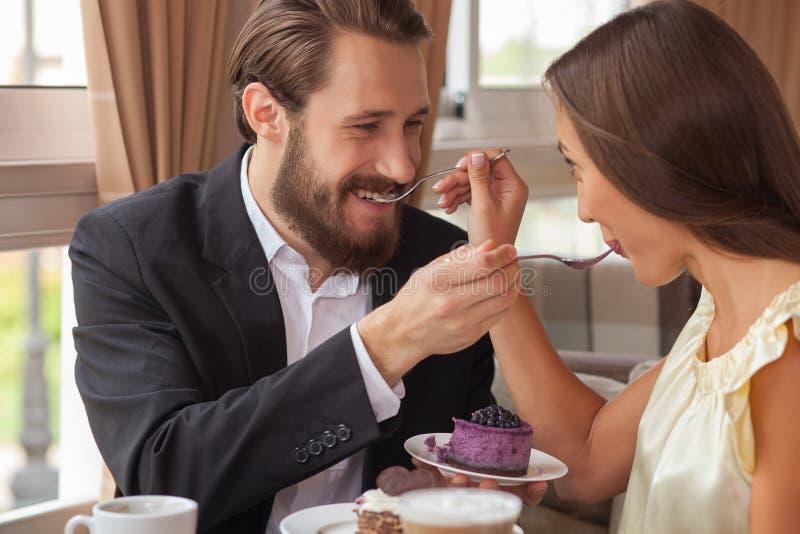 La giovane coppia amorosa allegra sta mangiando il dolce fotografie stock libere da diritti