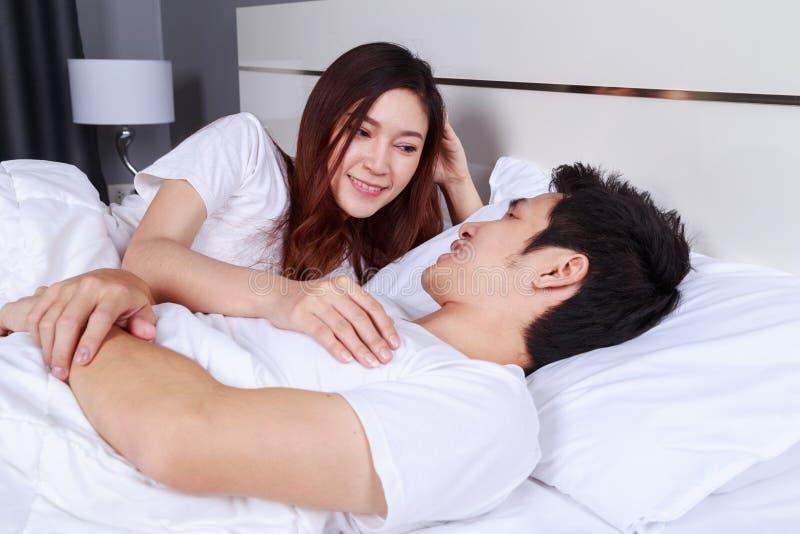 La giovane coppia che si trova in un letto e che guarda l'un l'altro osserva alla e immagine stock libera da diritti