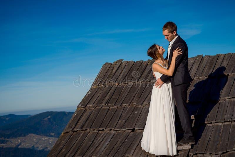 La giovane coppia di nozze abbraccia morbidamente sul tetto della casa di campagna Fondo meraviglioso del paesaggio della montagn fotografie stock libere da diritti