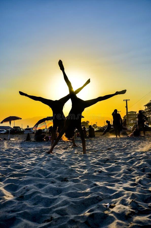 La giovane coppia fa il verticale alla spiaggia fotografia stock