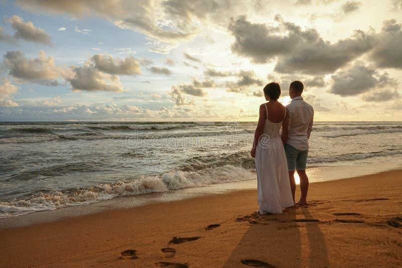 La giovane coppia nell'amore ad una data romantica incontra il tramonto sulla spiaggia, tenentesi per mano immagine stock