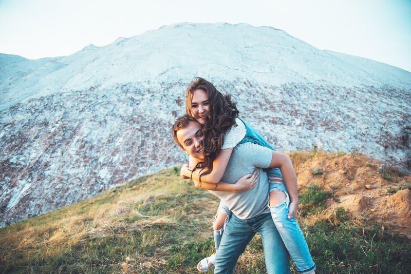 La giovane coppia nell'amore sta riposando insieme vicino al lago e le montagne, la bella donna caucasica e l'uomo si sono innamo immagine stock libera da diritti