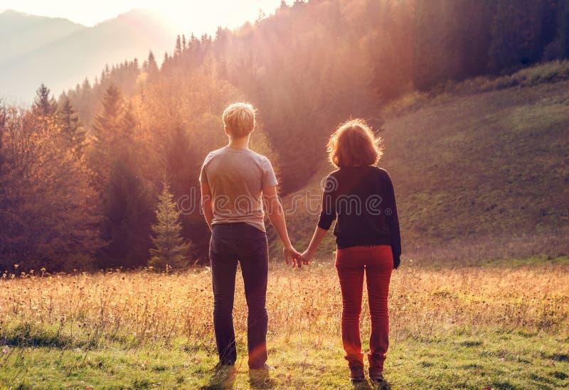 La giovane coppia prende le mani nel tempo del tramonto fotografie stock libere da diritti