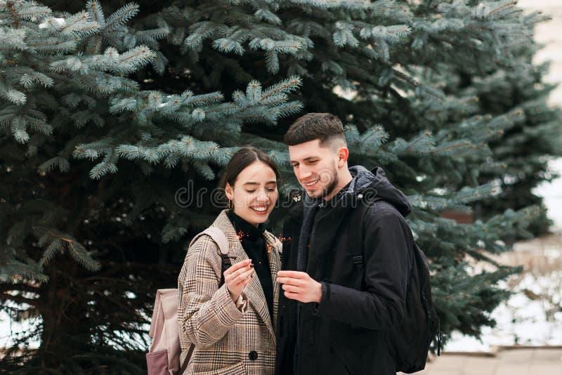 La giovane coppia romantica sta divertendosi all'aperto nell'inverno prima del Natale con le luci di Bengala fotografia stock libera da diritti