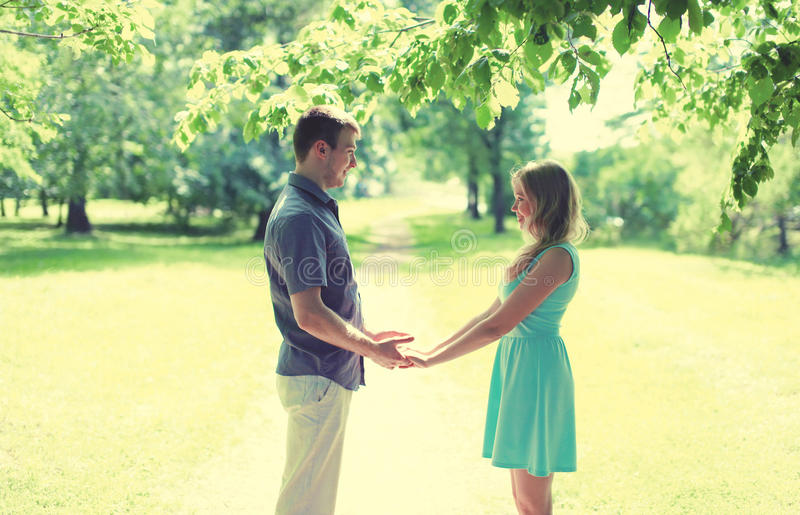 La giovane coppia sorridente felice nell'amore, si tiene per mano, relazioni, la data, le nozze - il concetto, colori morbidi d'a fotografie stock