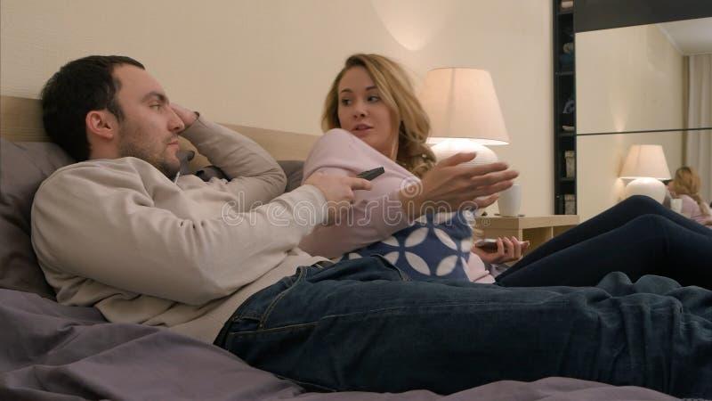La giovane coppia sta avendo una discussione heated a causa di geloso mentre ancora a letto fotografia stock