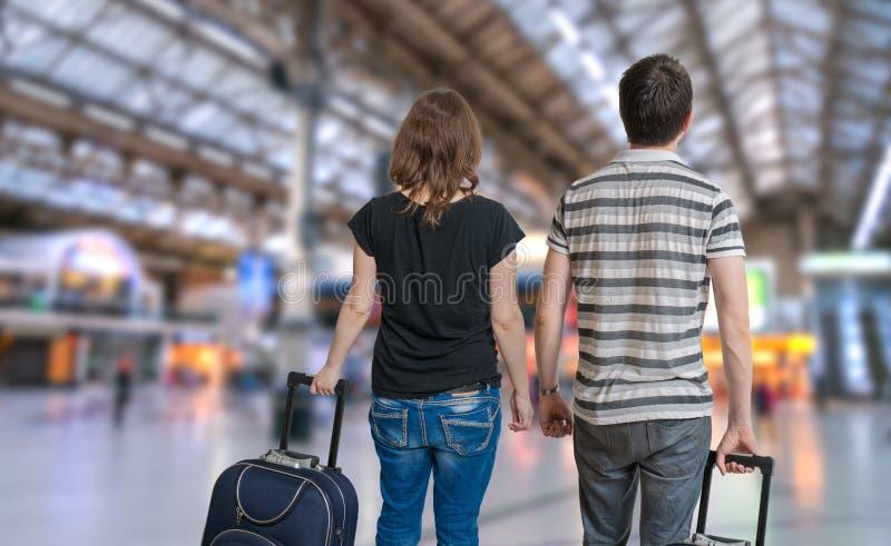 La giovane coppia sta viaggiando sulla vacanza Uomo e donna con bagaglio nella stazione ferroviaria fotografie stock