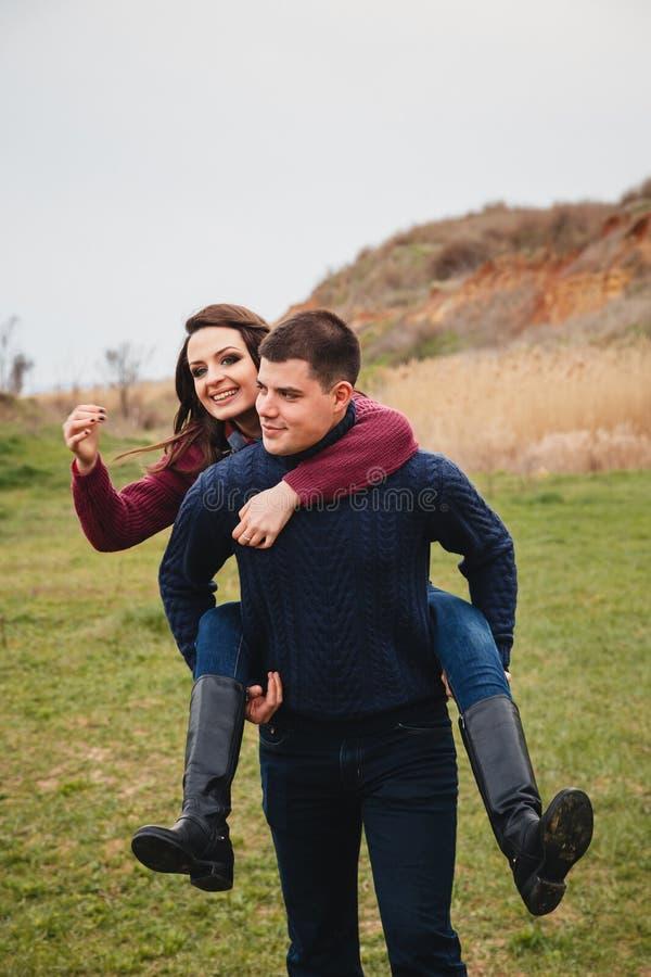 La giovane coppia sveglia sta scherzando, trasportando sulle spalle in mezzo al campo verde Buon giorno, felicità, amicizia, fest immagine stock