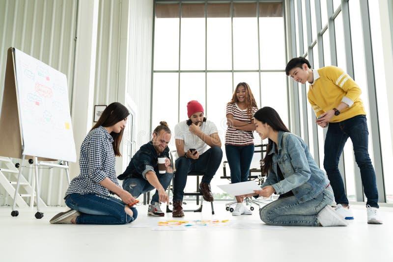La giovane diversa riunione dei gruppi creativa ed esaminare il piano del progetto presentano sul pavimento discutono o confronta fotografie stock