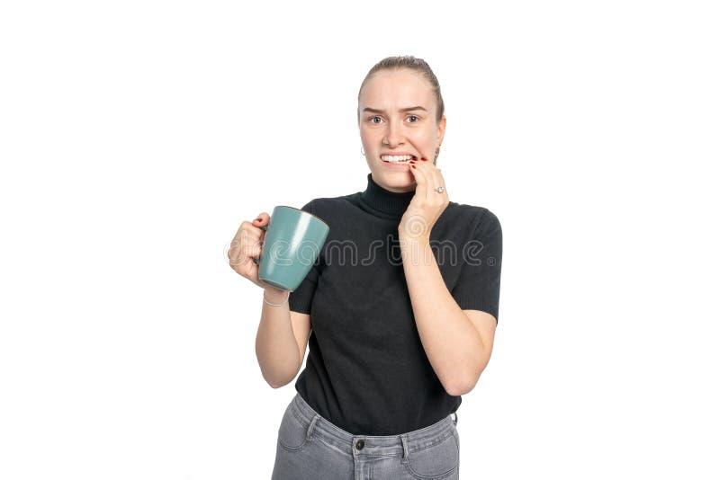 La giovane donna è sensibile al calore quando beve le bevande calde fotografia stock