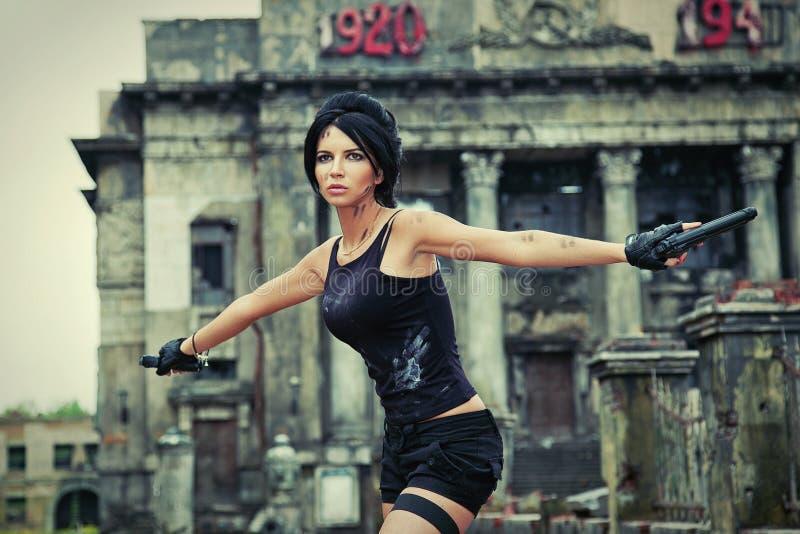La giovane donna è un agente segreto con una pistola in una città rovinata fotografia stock libera da diritti