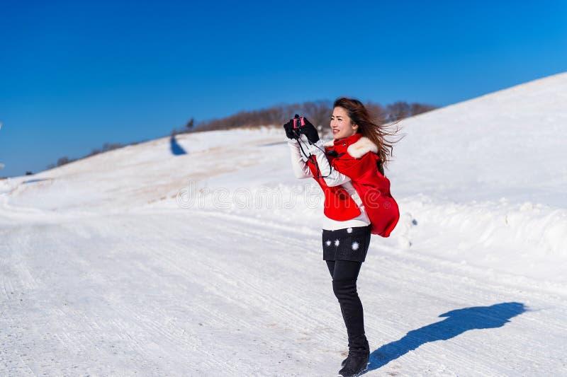 La giovane donna è una felicità con la macchina fotografica nell'inverno fotografie stock libere da diritti