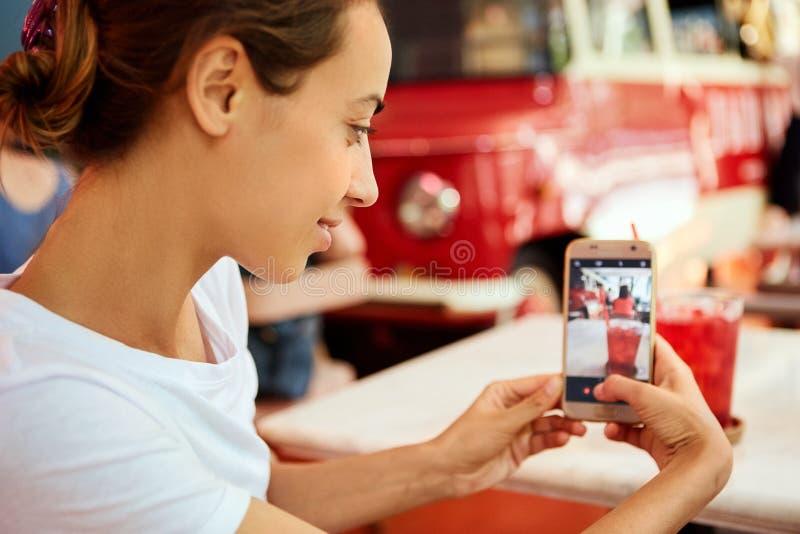 La giovane donna abbronzata graziosa in maglietta bianca sta sedendosi in caffè e sta prendendo un'immagine sul telefono, bevent fotografia stock libera da diritti