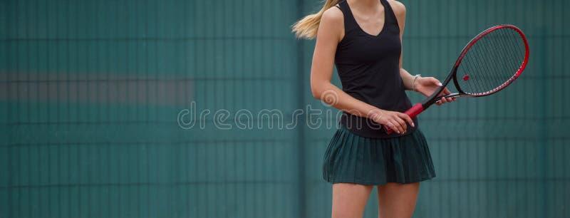 La giovane donna adatta gioca a tennis all'aperto sul campo arancio del tennis fotografie stock