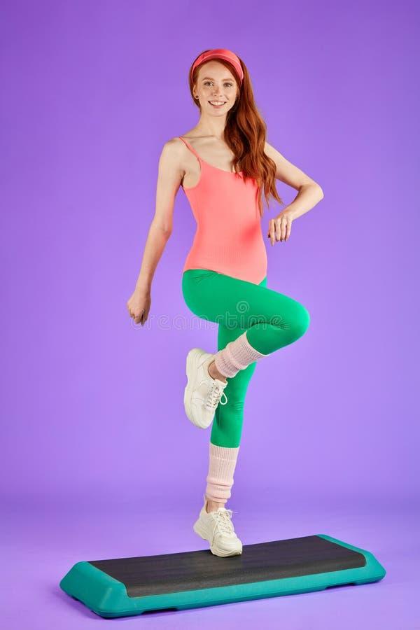 La giovane donna adatta graziosa fa i punti alla piattaforma di forma fisica immagine stock