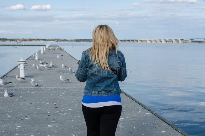 La giovane donna adulta cammina fuori su un pilastro vicino al fiume di Choptank a Cambridge Maryland un giorno di molla soleggia fotografia stock libera da diritti