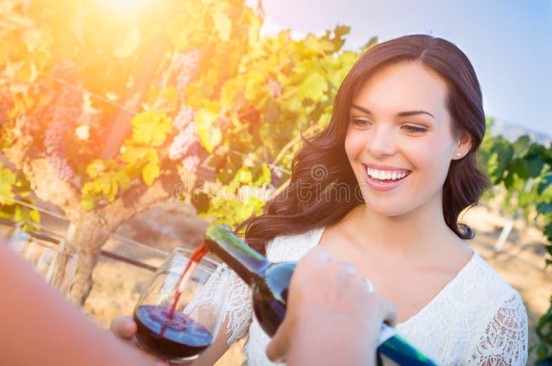 La giovane donna adulta sorridente che gode dell'assaggio del bicchiere di vino versa nella vigna con gli amici immagine stock libera da diritti